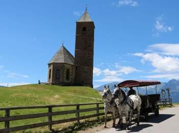 Carrozza trainata da cavalli di fronte alla chiesa di Santa Caterina ad Avelengo