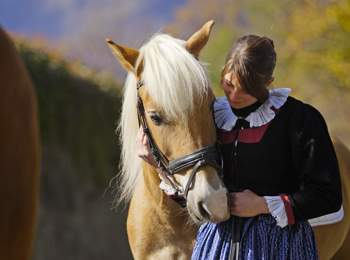 Haflinger & woman in traditional costume